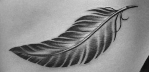 Перо - татуировка на ребрах девушки