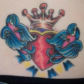 Тату корона над сердцем и две птицы на копчике у девушки