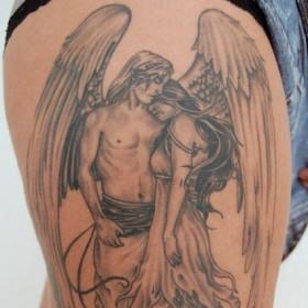 Тату на бедрах девушки - ангел в виде парня и девушка