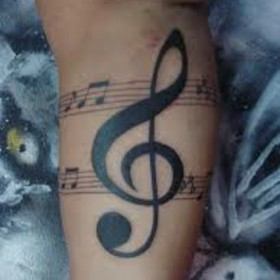 Тату на бицепсе у парня - скрипичный ключ и ноты