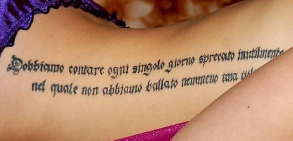 Тату на боку девушки - надпись на латыни