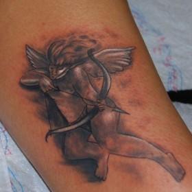 Тату на голени девушки - ангел-купидон с луком и стрелой