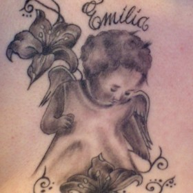 Тату на груди девушки - ангел, лилии и надпись в виде имени