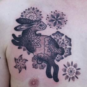Тату на груди парня - заяц и цветы