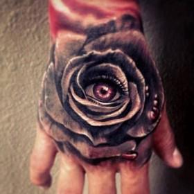 Тату на кисти парня - роза и глаз