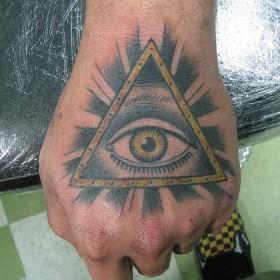 Тату на кисти у парня - пирамида с глазом