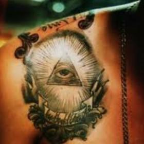 Тату на ключице парня - пирамида с глазом