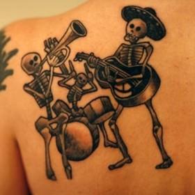 Тату на лопатке девушки - скелеты
