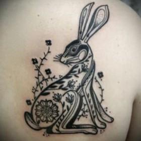 Тату на лопатке девушки - заяц с цветком