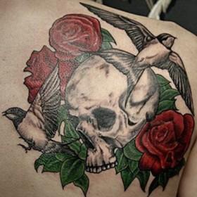 Тату на лопатке парня - череп, ласточки и розы
