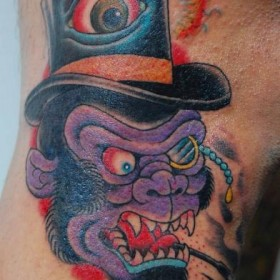 Тату на ноге парня - обезьяна в шляпе