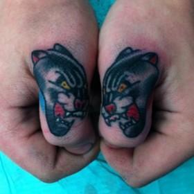 Тату на пальцах девушки - головы пантер
