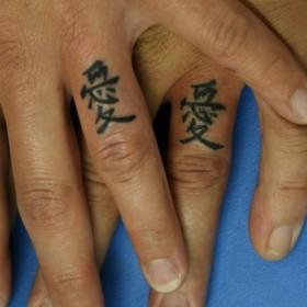 Тату на пальцах девушки и парня - китайские иероглифы