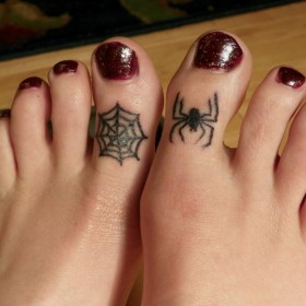 Тату на пальцах девушки - паутина и паук