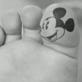 Тату на пальце девушки - голова мыши Микки Маус