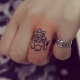 Тату на пальце девушки - лев