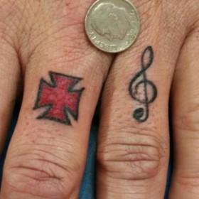 Тату на пальце у парня - скрипичный ключ