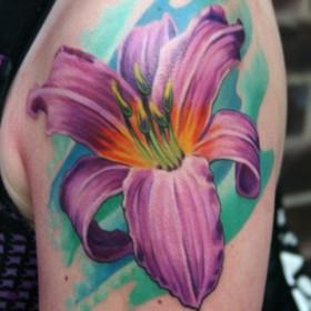 Тату на плече девушки в виде фиолетовой лилии