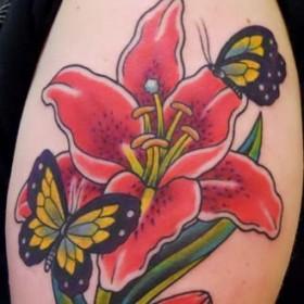 Тату на плече девушки в виде лилии и бабочек
