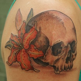 Тату на плече девушки в виде лилии и черепа