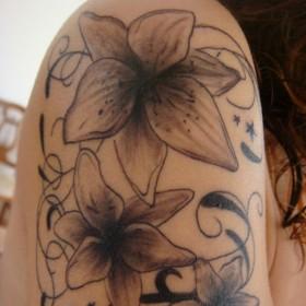 Тату на плече девушки в виде лилий