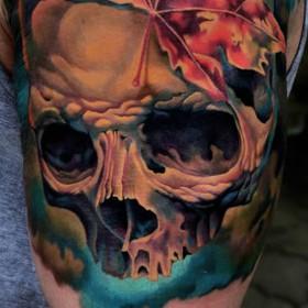 Тату на плече парня - череп и листья