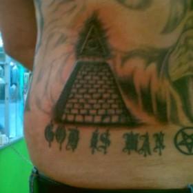 Тату на пояснице парня - пирамида с глазом
