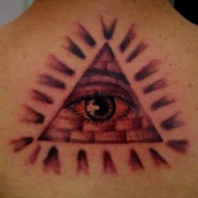 Тату на позвоночнике парня - пирамида с глазом