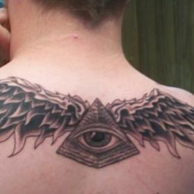 Тату на позвоночнике парня - пирамида с глазом и крыльями