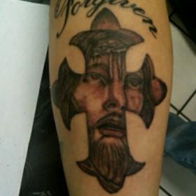 Тату на предплечье парня - крест и лицо Иисуса в нем