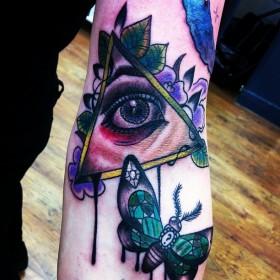 Тату на руке девушки - пирамида с глазом и мотылек