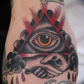 Тату на руке девушки - пирамида с глазом и рукопожатие