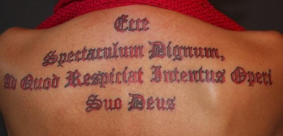 Тату на спине девушки - надпись на латыни