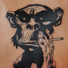 Тату на спине парня - обезьяна с сигаретой