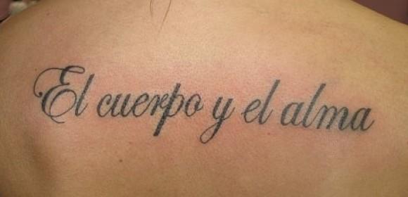 Тату на спине у девушки - надпись на латыни