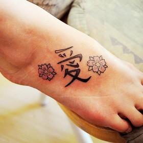 Тату на ступне девушки - китайские иероглифы и сакура