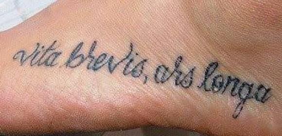 Тату на ступне девушки - надпись на латыни