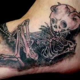 Тату на ступне парня - скелет