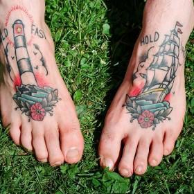 Тату на ступнях парня - маяк и корабль