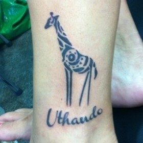 Тату на щиколотке девушки - жираф и надпись