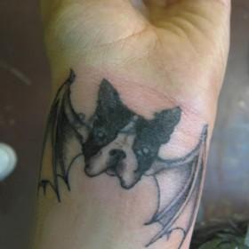 Тату на запястье у девушки - собака с крыльями летучей мыши
