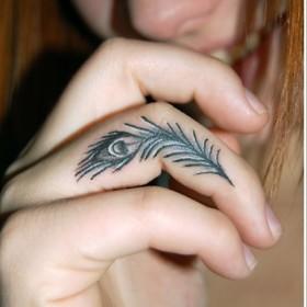 Тату у девушки на пальце в виде пера павлина