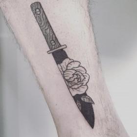 Татуха ножа с розой на предплечье мужчины