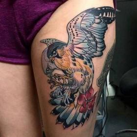 Татуировка ястреба на бедре девушки
