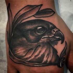 Татуировка ястреба на кисти парня