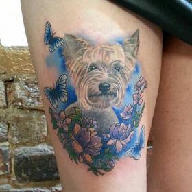 Татуировка на бедре девушки - песик