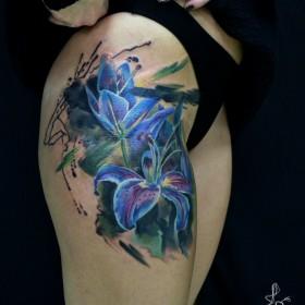 Татуировка на бедре у девушки - лилии