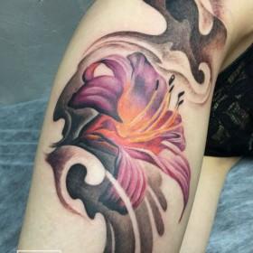 Татуировка на бедре у девушки - лилия