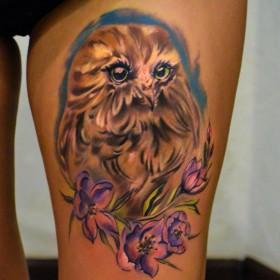 Татуировка на бедре у девушки - сова и цветы