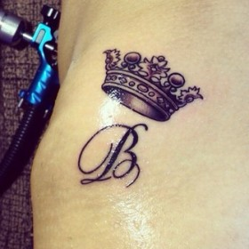 Татуировка на боку у девушки - корона буква В